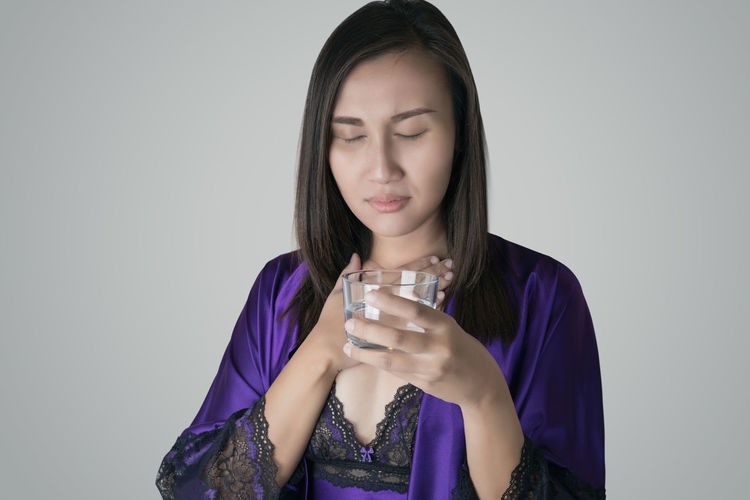Asian women drinking water because of the dry throat on a gray background SORE Throat Dry Woman Neck Pain Feel Symptom Dried Ache Sick Cold Flu Bad Healthcare And Medicine