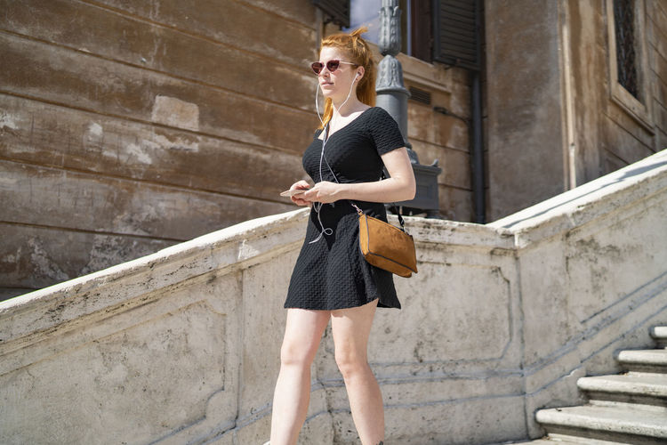Full length of young woman wearing sunglasses standing outdoors