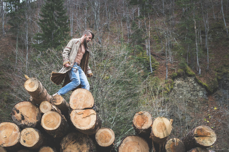 Young man walking on logs of wood in forest