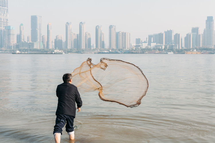 Rear View Of Man Throwing Fishing Net In Yangtze River By City