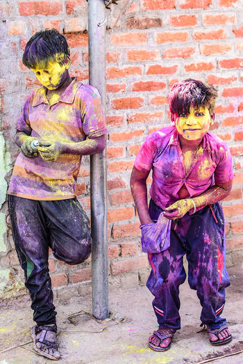 Full length of children covered in multi colored powder paint
