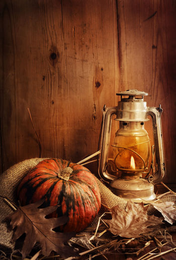 Close-up of pumpkin and illuminated lantern against wooden wall