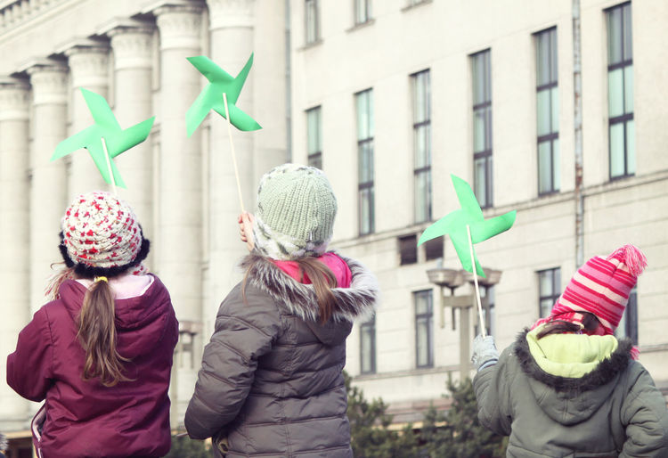 Rear view of girls playing with pinwheel toys by building