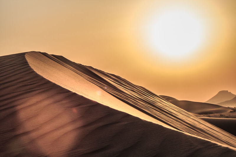 Scenic view of sand dunes against sky at sunset