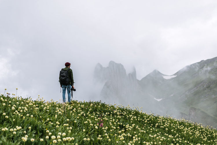 Lost In The Landscape Adventure Beauty In Nature Day Flower Full Length Growth Landscape Leisure Activity Men Mountain Mountain Range Nature One Person Outdoors People Real People Rear View Scenics Sky Standing Be. Ready.