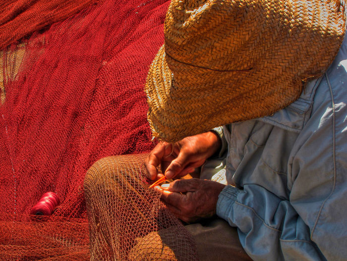 Man Sewing Fishing Net During Sunny Day