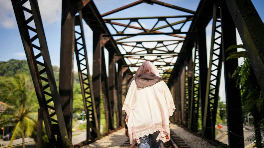 Rear View Of Woman Walking On Railway Bridge
