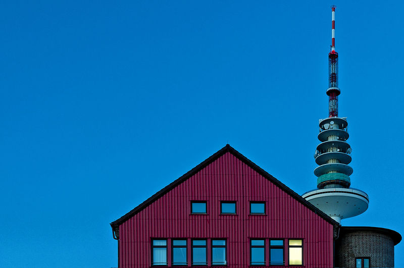 Low angle view of maroon cottage and heinrich-hertz-turm against clear blue sky