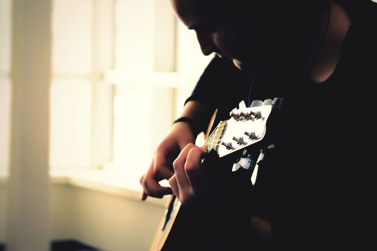 Close-up of man playing guitar at home