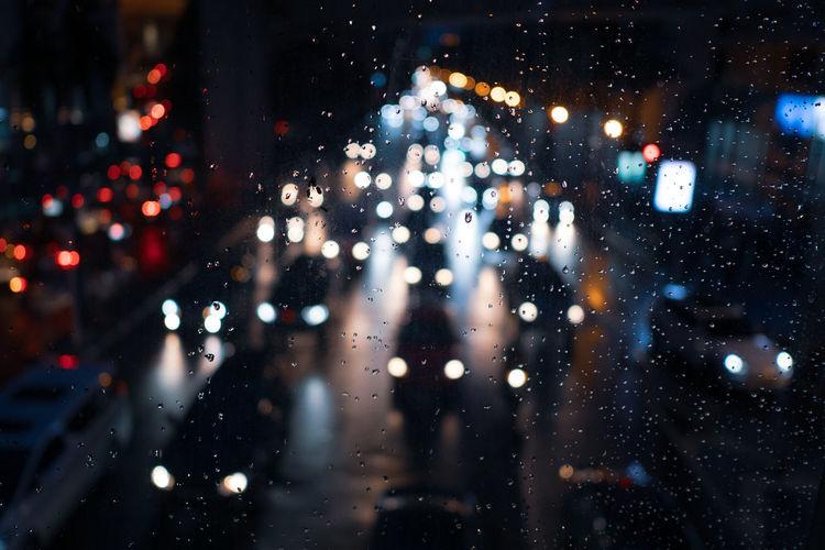Illuminated vehicles seen through wet window in city at night