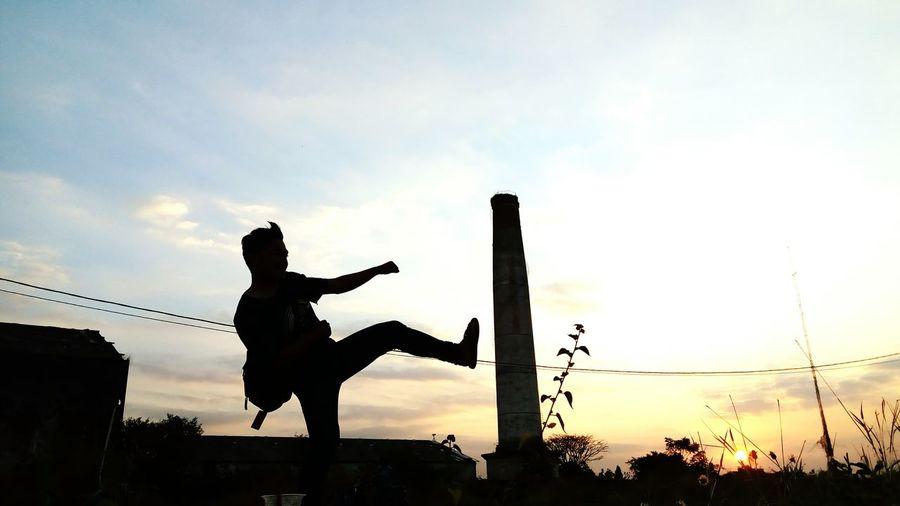 Optical illusion of silhouette man kicking smoke stack against sky during sunset