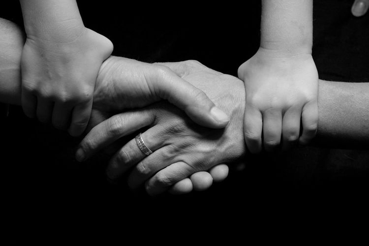 Cropped image of people with holding hands against black background