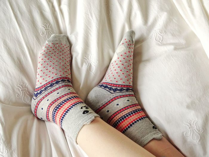 Low Section Of Woman Wearing Socks Relaxing On Bed At Home