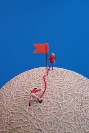 Man with red umbrella against clear blue sky
