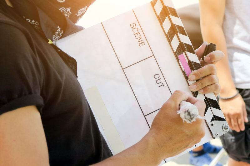 Midsection Of Woman Writing On Clapperboard