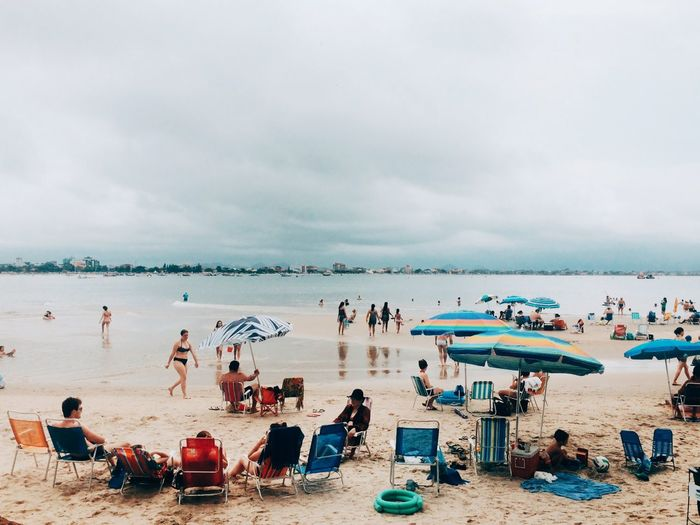 People At Beach Against Cloudy Sky
