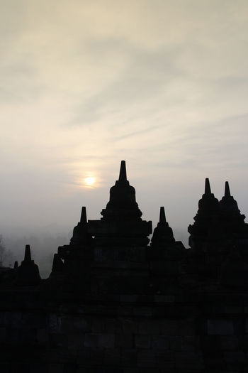 Silhouette Borobudur Temple with the mysteries forest surrounding during sunrise, Yogyakarta, Indonesia Ancient Borobudur Temple Java Yogyakarta Ancient Civilization Architecture Belief Buddhism Building Building Exterior Built Structure Dawn Fog Forest History Mount Merapi No People Place Of Worship Religion Religious Architecture Silhouette Sky Spirituality Sunrise Sunset