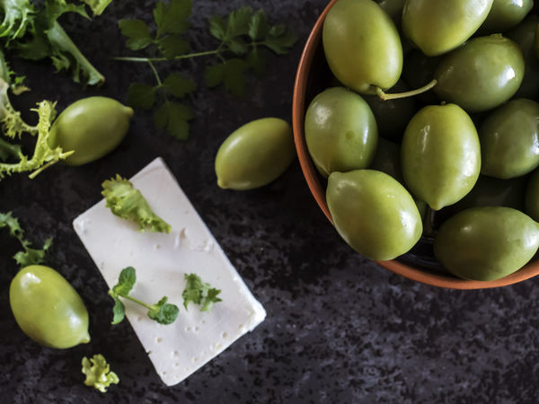 High angle view of Feta cheese with olives and green herbs on gray marble background Background Cheese Close-up Day Feta Food Food And Drink Freshness Fruit Granny Smith Apple Gray Green Green Color Green Olive Healthy Eating Herbs High Angle View Indoors  Leaf Marble No People Olives