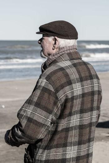 Man wearing hat standing on beach