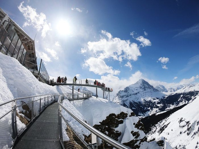 People walking on footbridge by snow covered mountains against sky