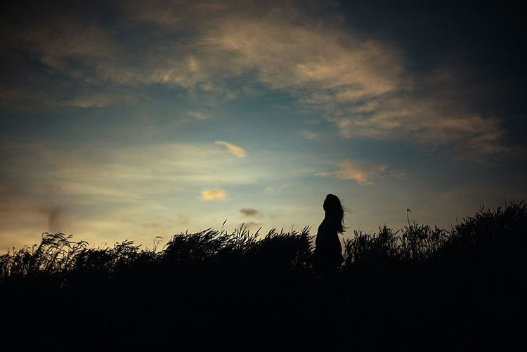 Silhouette of woman against sunset sky