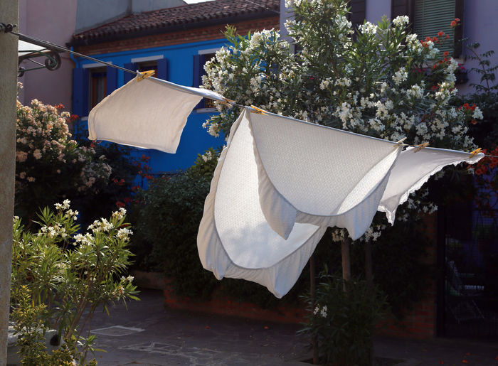 White clothes drying on clothesline by building