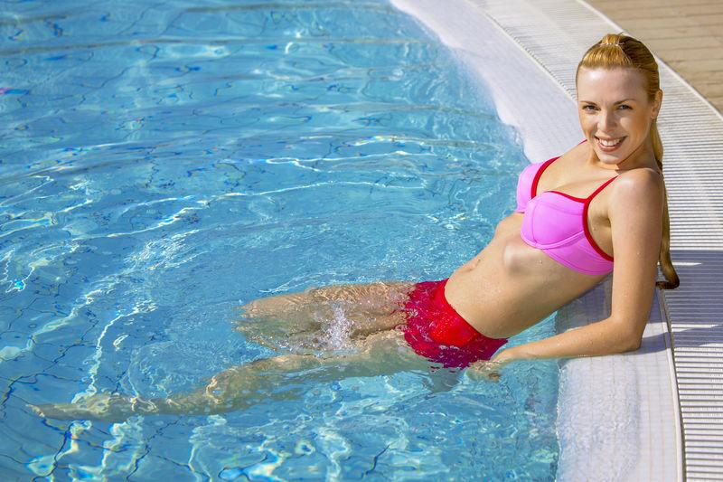 Portrait Of Cheerful Woman Wearing Bikini In Swimming Pool