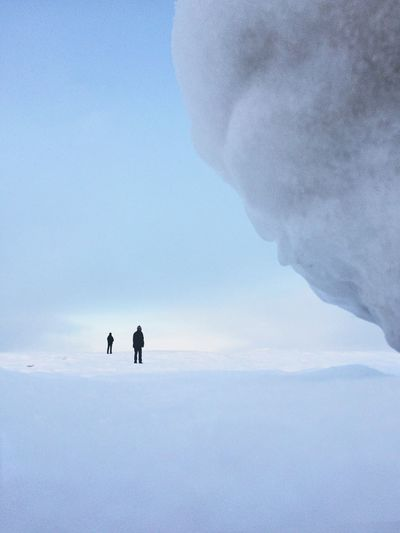Two people on standing on snow covered field against sky