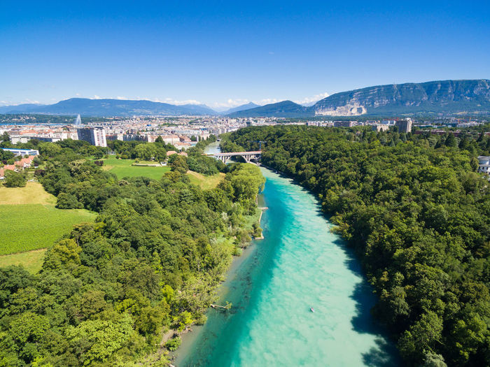 Aerial view of river amidst trees against clear blue sky