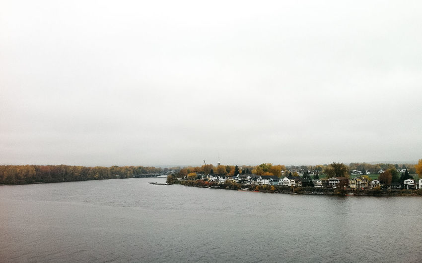 Scenic view of lake and town against sky