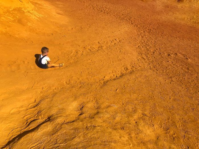 High angle view of baby boy sitting at desert