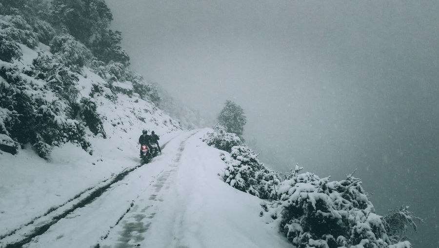 People riding in snow on motorbikes