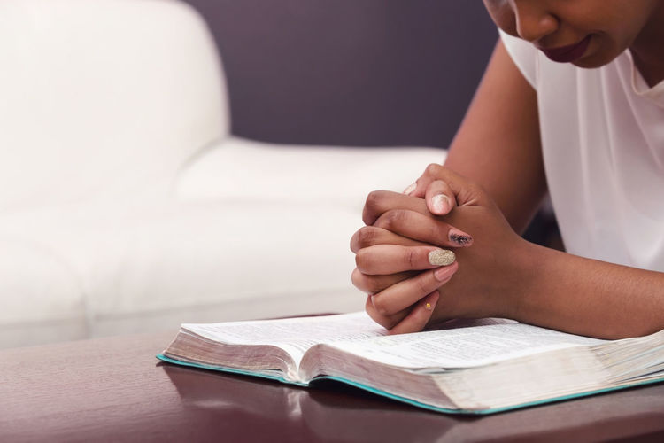 Cropped Image Of Young Woman Praying At Home