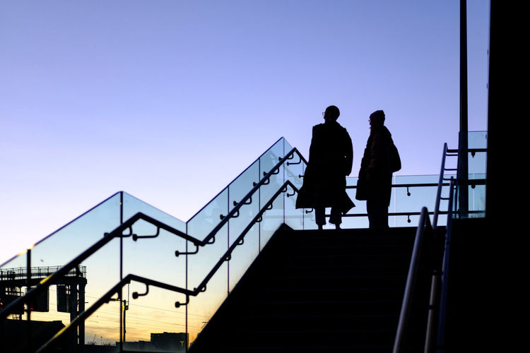 Silhouette people walking on staircase against clear blue sky