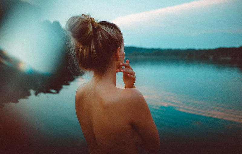 Rear View Of Naked Woman Standing Against Lake