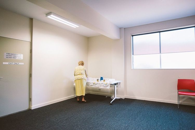 Full length rear view of woman standing by table in room