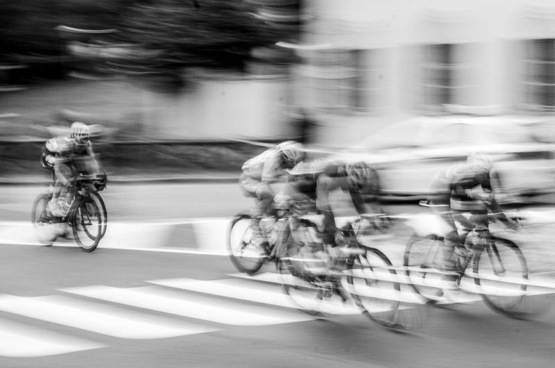 Blurred Motion Of People Riding Bicycle On Road