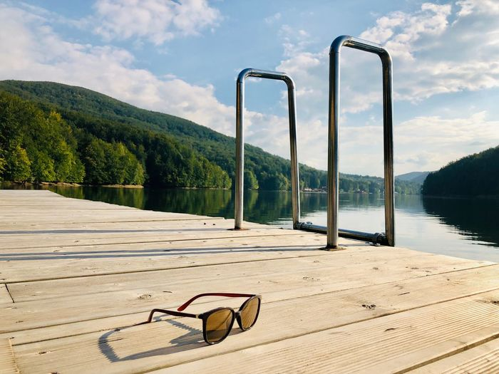 Black sunglasses on wooden pontoon near a lake surrounded by green forest