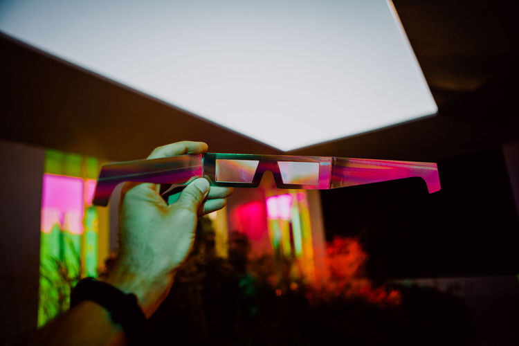 Man Hand Holding Polarised Paper Glasses Inside the Colorful Lighting Room with Plants in the Background Finger Light Close-up Lighting Equipment Home Interior Architecture Indoors  One Person Hand Multi Colored Illuminated Holding Night Lifestyles Paper Glasses Colors Dream Cinema Film 3D Virtual Reality Fantasy Disco Colorful Humanity Meets Technology