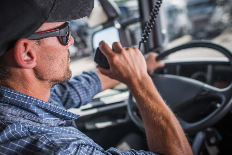 Man holding walkie-talkie while sitting in truck