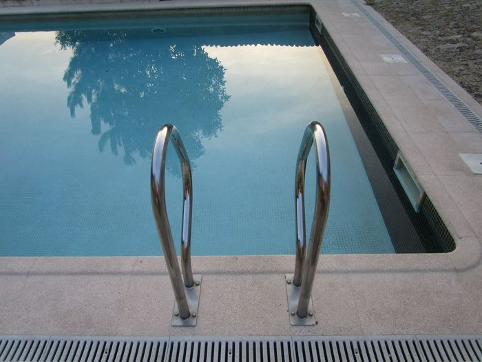 Swimming pool with metallic ladder