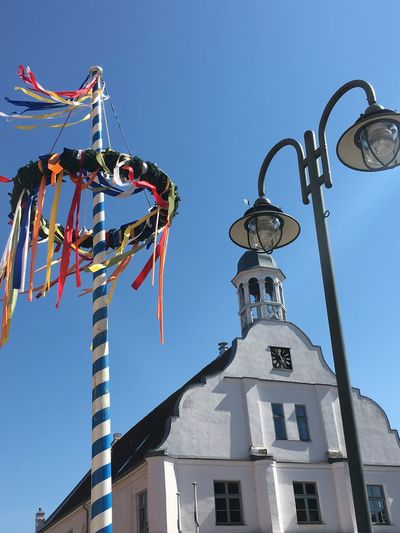Low angle view of maypole against blue sky