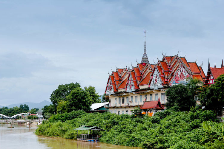 Traditional building by river against sky