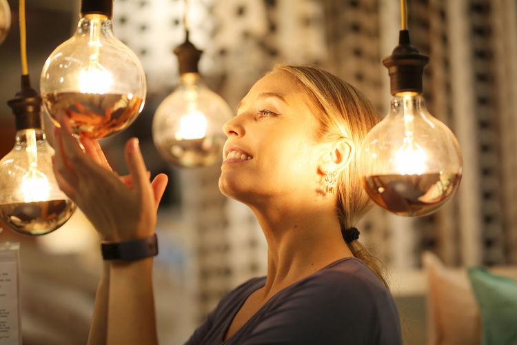 Portrait of woman holding illuminated light bulb