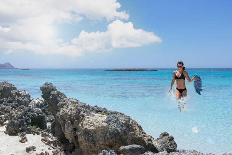 Woman on rocks by sea against sky