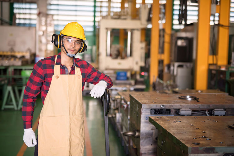Smiling asian factory young worker with plaid red shirt, helmet, safety glasses at trolley