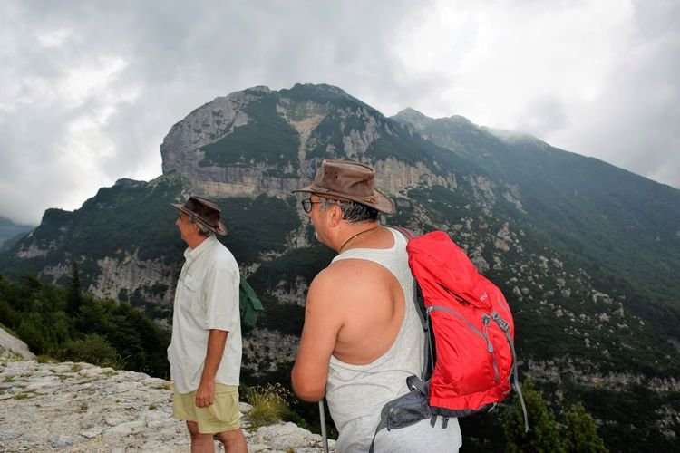Male friends hiking on mountain against cloudy sky