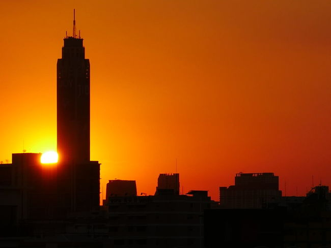 Silhouetted city Sunset Skyscraper Architecture Urban Skyline City Cityscape Downtown District Building Exterior Travel Destinations Orange Color Tower Dramatic Sky Built Structure Travel Office Building Exterior Modern Night Illuminated Sky Tourism