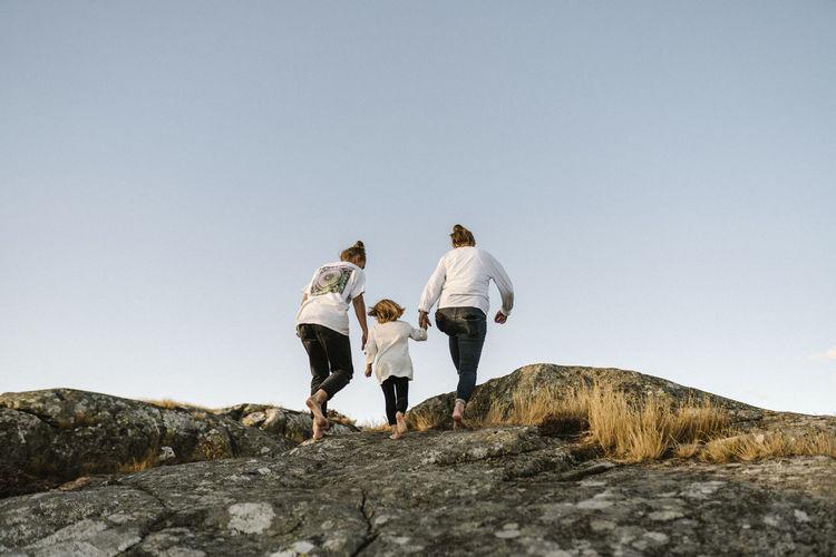 Rear view of men walking on rock against clear sky
