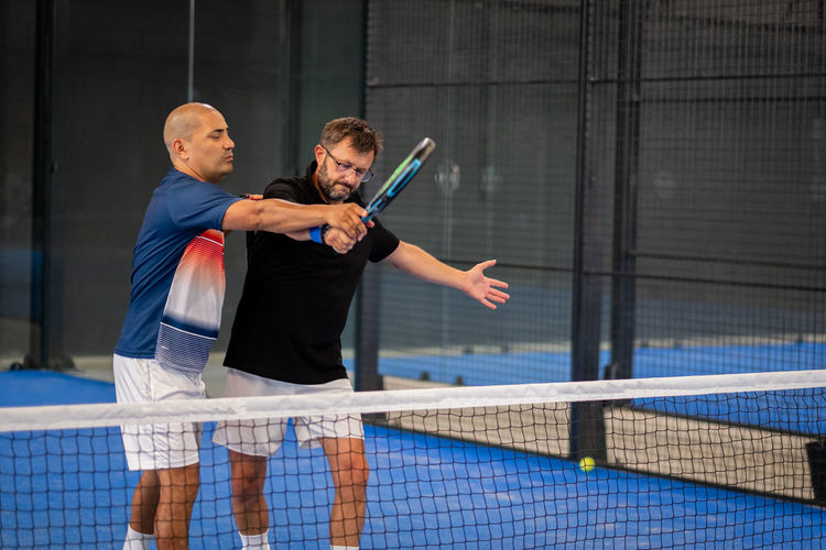 Monitor teaching padel class to man, his student - trainer teaches boy how to play padel on indoor